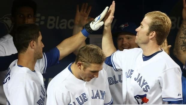 Yan Gomes, left, is congratulated by Casey Janssen after hitting a game-tying solo home run in the ninth inning with two outs to help the Blue Jays come from behind and beat the Minnesota Twins on Monday.
