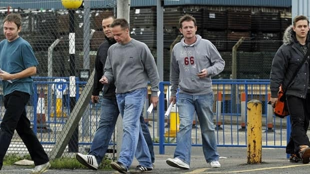 Workers leave the Ford stamping plant after their shift in Dagenham, Essex, Thursday.
