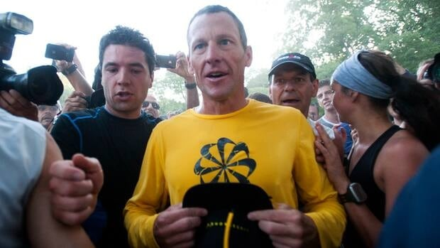 Lance Armstrong is swamped by supporters following a run in Mont Royal Park in Montreal on Aug. 29.