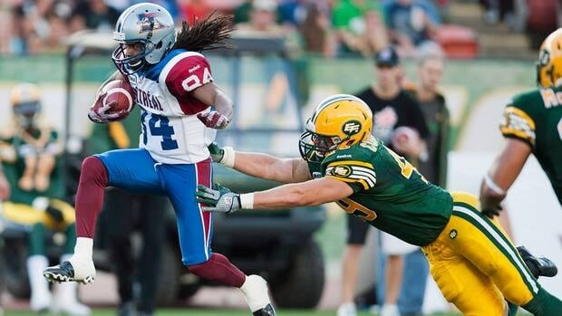Montreal Alouettes Trent Guy leaps away from Edmonton Eskimos Mike Cornell during the first half of their game last August.