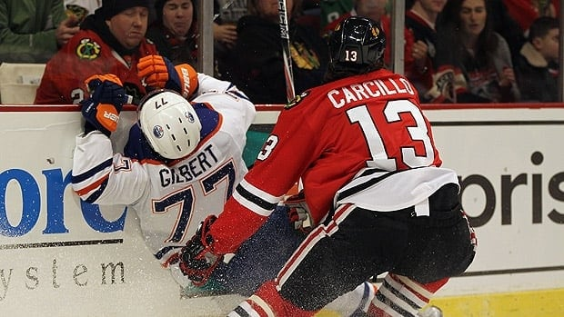 Dan Carcillo of Chicago hits Oilers defenceman Tom Gilbert on the play in question in Monday's game.