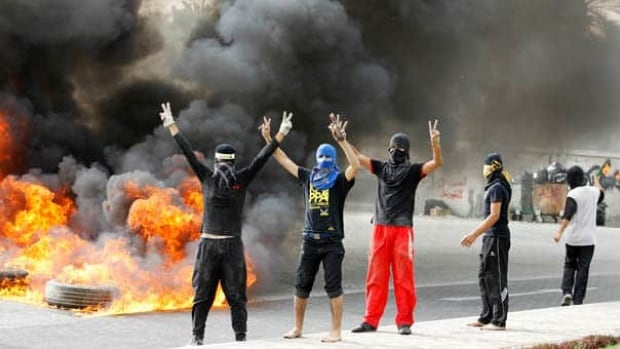 Anti-government protesters flash victory signs as they burn tires in Budaiya, west of Manama, early Sunday.