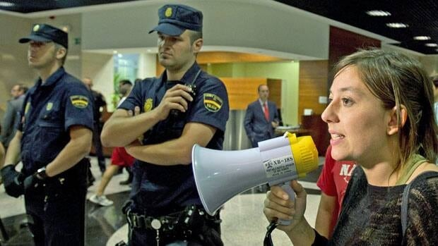 A protester addresses demonstrators opposed to banks' evictions of families from their homes for mortgage arrears in Madrid on Friday. European politicians worry that Spain won't be able to raise enough money to bail out its debt-laden banks on its own.