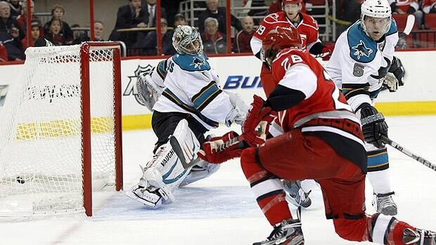 Carolina's Justin Faulk fires the puck past San Jose goalie Thomas Greiss as Sharks defender Colin White looks on Friday.