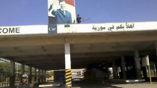 This image made from amateur video purports to show a Syrian rebel defacing a picture of President Bashar Assad above the Bab al-Hawa border crossing with Turkey. Rebels seized two of the country's border crossings.