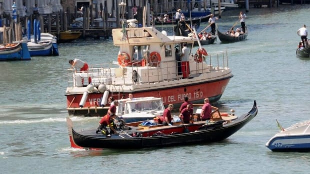 Firefighters in Venice transport the gondola after it crashed with a ferry boat.