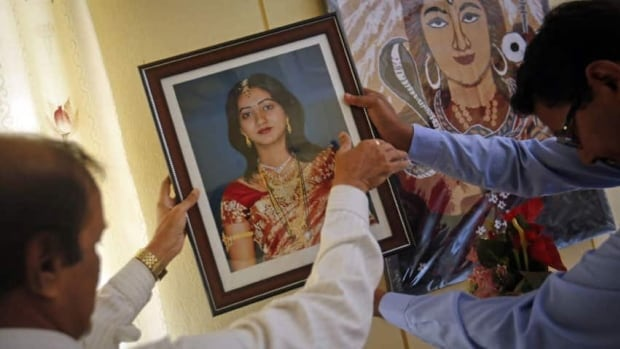 Andanappa Yalagi, left, father of Savita Halappanavar, is helped by a family friend as he hangs her portrait at their house in Belgaum in the southern Indian state of Karnataka  Halappanavar, who was refused a termination, died from blood poisoning in an Irish hospital.