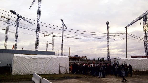 Workers stand outside the entrance of the MUHC superhospital construction site Tuesday morning in Montreal.