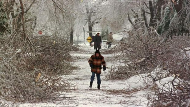 Pedestrians make their way past broken branches as clean-up operations begin in Montreal in January 1998.