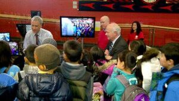 CBC reporter Alan Waterman and chief correspondent Peter Mansbridge talk to visitors during the Open House at the CBC studio in Vancouver on Friday.