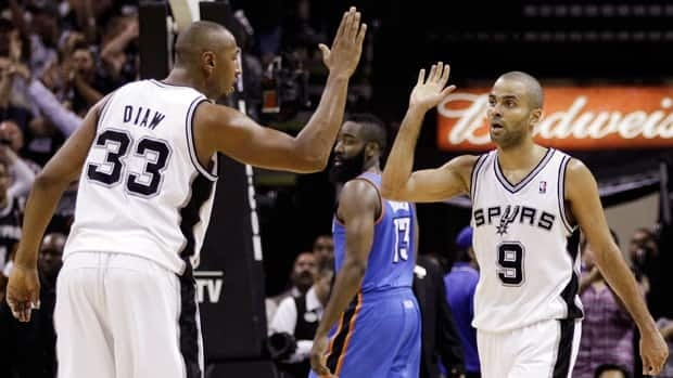 San Antonio Spurs power forward Boris Diaw (33) congratulates Tony Parker (9) after Parker scored against the Oklahoma City Thunder during the second half of Game 2 on Tuesday in San Antonio. The Thunder's James Harden (13) is at rear.