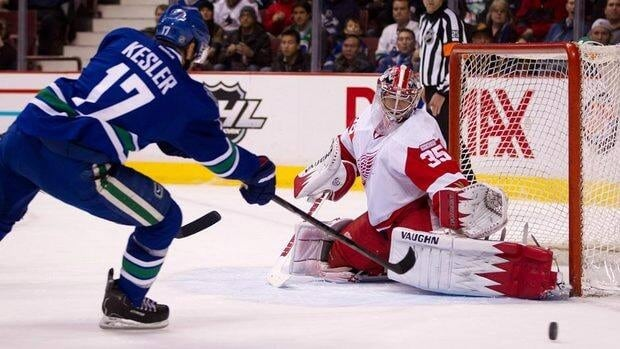 Detroit Red Wings' goalie Jimmy Howard, right, stops Vancouver Canucks' Ryan Kesler during the first period Thursday.