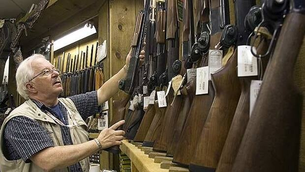 A man replaces a shotgun in the rack in a downtown Montreal outdoor store.