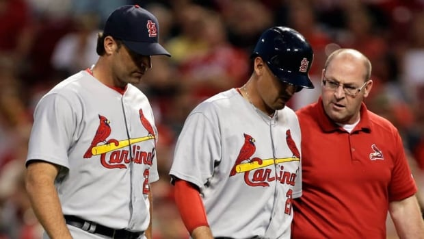 St. Louis Cardinals first baseman Allen Craig, centre, walks off the field with manager Mike Matheny and a trainer after Craig was injured against the Cincinnati Reds on Wednesday.