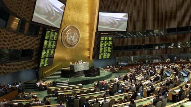 A hand is shown on a video screen, pushing a button to vote on a Saudi Arabian-sponsored draft resolution against Syria at the UN General Assembly on Friday.