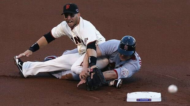 Matt Holliday (7) of the St. Louis Cardinals slides into second, knocking over Marco Scutaro (19) of the San Francisco Giants in the first inning of Game 2 on Tuesday.