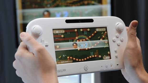 A participant at the E3 2012 video game expo tries out Nintendo's Wii U GamePad. The Japanese company is expected to reveal more details about the Wii U games console Thursday, including when it will be available in stores and how much it will cost.