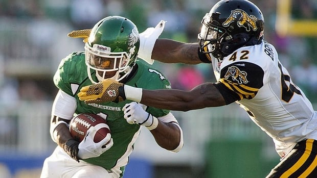 Hamilton Tiger-Cats defensive back Raymond Brown attempts to tackle Saskatchewan Roughriders running back Kory Sheets during the second half of CFL football action at Mosaic Stadium on Sunday, July 21, 2013 in Regina.