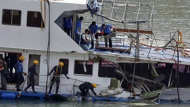 A group of firemen and police officers investigate on a salvaged boat which sank after colliding with a ferry near Lamma Island, off the southwestern coast of Hong Kong Island on Wednesday.