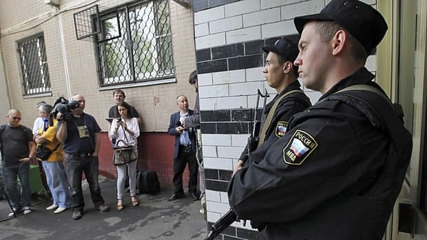 Russian police officers guard the entrance of the building where opposition leader Alexei Navalny resides during a police search in Moscow on Monday.