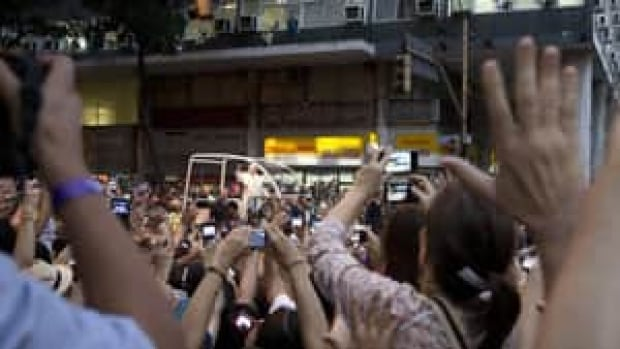 People wave to Pope Francis riding in his popemobile through Rio de Janeiro, Brazil. The pontiff arrived for a seven-day visit in Brazil, the world's most populous Roman Catholic nation.