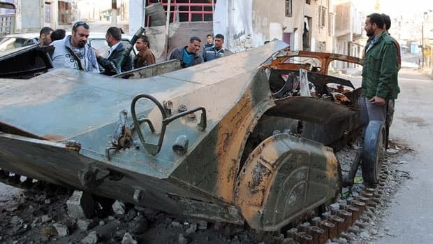 Syrians look at a destroyed Syrian armoured vehicle in Homs province, central Syria. Fighting between rebels and the army resumed Saturday, with much of the violence focusing on the northeastern town of Saraqeb.