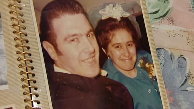Sheila Oakley holds a wedding photo of her and her husband Glenn.
