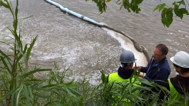 Crews put up booms on the river to try to contain the material coming out of the sewer outlet.