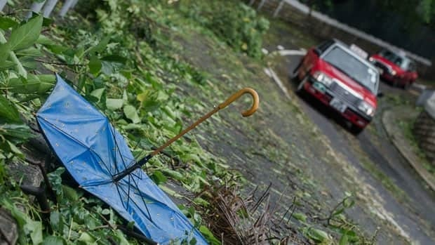 Taxis drive past a broken umbrella among tree branches in the aftermath of Typhoon Vincente in Hong Kong. More than 100 people were injured and trees were ripped from the ground.
