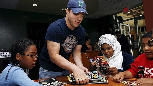Green Lantern writer and DC Entertainment COO Geoff Johns hands out comic books to Detroit kids at the Arab American National Museum in Dearborn, Mi in September. The company is moving to sell its monthly titles in computer tablet form in a bid to attract new readers.