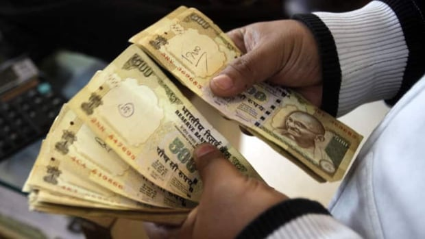 An Indian customer counts Indian rupee notes at a foreign currency exchange in Bangalore, India. The rupee has plunged to new lows against the U.S. dollar on a near daily basis, showing the pressure of a current account deficit that has swelled from high import costs.