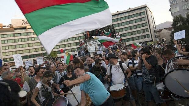 A protester waves the Bulgarian national flag during an anti-government demonstration in front of the parliament building in Sofia Wednesday after police freed more than 100 lawmakers, ministers and journalists from inside the building.