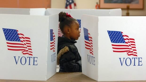 Chyniah Woods, 8, watches her mother Kesia Woods vote for the very first time at the Concord 15th precinct at Rosedale Highrise in Elkhart, Ind. Tuesday, Nov. 6, 2012.