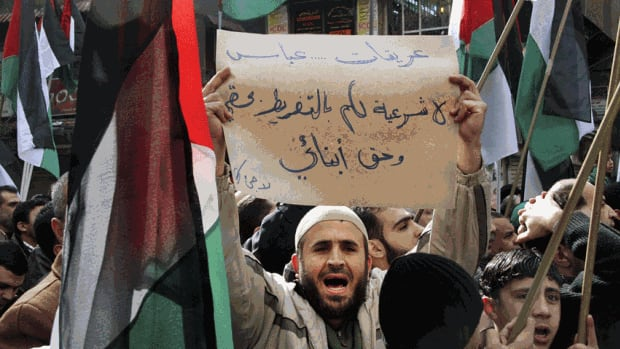 "A Palestinian protester in Syria's Yarmouk refugee camp carries a banner that reads in Arabic, ""Erekat, Abbas, no legitimacy for you to give up my right and my children right,"" during an anti-government rally in 2011. The camp was struck by mortars Thursday night, activists say."
