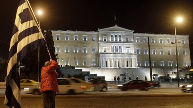A protester raises a Greek flag during an anti-austerity rally in front of the parliament in Athens on Saturday.