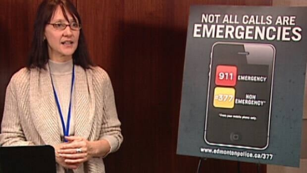 911 supervisor Kim Pudde stands beside a sign showing the numbers people can dial for emergency and non-emergency situations