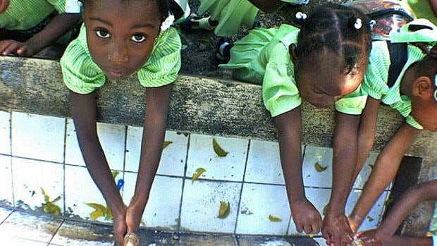 With cholera still rampant, students at Ecole Republiques des Etats-Unis take pains to wash their hands often. The school, built of plywood, is one of the bright spots, David Common found.