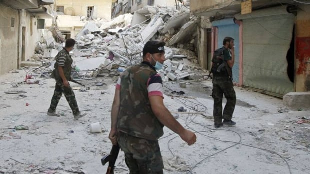 Free Syrian Army fighters walk in Salaheddine neighborhood in central Aleppo on Monday. A Syrian regime envoy is in China today to hold talks.