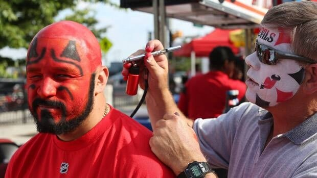 New Jersey Devils' fan David Rivera, left, of Jersey City, N.J., has his head airbrushed before Game 2 on Saturday in Newark, N.J.