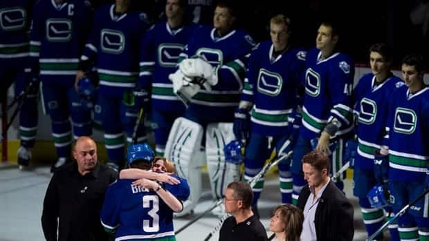 Vancouver Canucks defenceman Kevin Bieksa (3) hugs Shelley Crawford, mother of former Vancouver Canuck Rick Rypien, during a ceremony prior to a game in Vancouver on Oct.18, 2011.