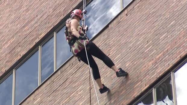A rappeller scales down the side of Atlantic Place in downtown St. John's as part of the 2013 Easter Seals Drop Zone.