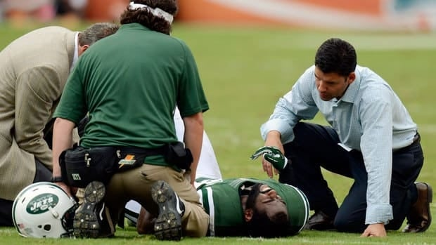 Jets trainers attend to cornerback Darrelle Revis after he went down in the second half of Sunday's win at Miami.