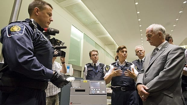 Public Safety Minister Vic Toews, right, watches a CBSA demonstration of drug-detecting technology at Pearson airport in Toronto last summer. Toews has ordered a halt to audio monitoring of travellers until a privacy assessment can be conducted following concerns from the privacy commissioner's office.