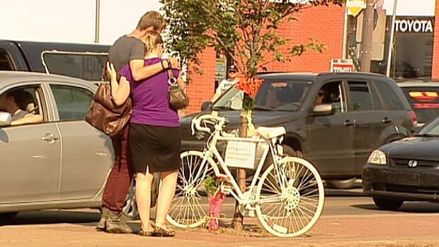 Two people leave flowers at a 'ghost bike' marking the death of cyclist on Whyte Avenue Monday morning.