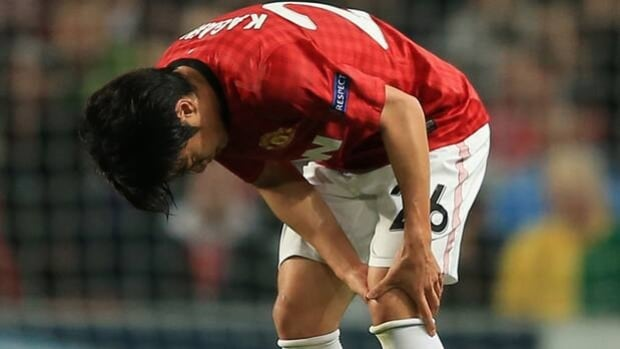United midfielder Shinji Kagawa clutches his left knee in pain at Old Trafford on Tuesday.