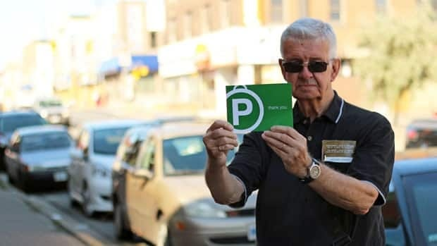 Dale Wilson holds up one of postcards the city distributes to get feedback on the free parking program.