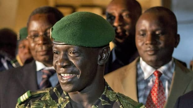 Junta leader Capt. Amadou Haya Sanogo, front, speaks to the press. In a public about-face amid mounting international pressure, the rebels have pledged to reinstate Mali's 1992 constitution and hold democratic elections.