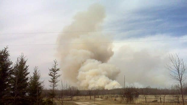 Smoke from a wildfire eight kilometres west of Teulon, Man., on Friday. Lois Downey's house, garage, workshop and barn were destroyed in the blaze.