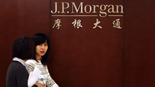 Employees walk past the company logo at the JPMorgan Beijing office. The investment bank is the subject of a probe into bribery allegations over its hiring of figures connected to influential Chinese politicians.
