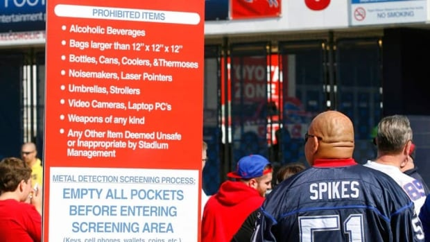 In this Sept. 16, 2012 file photo, a Buffalo Bills fan reads the security screening sign at a security checkpoint before entering the stadium for an NFL game against the Kansas City Chiefs. The NFL is tightening stadium security starting this preseason, limiting the size and type of bags fans can bring to the game. The restrictions are designed to enhance security while speeding up entry into stadiums.